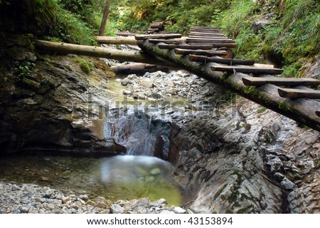 A small waterfall on a forest stream with boardwalk in Slovakian paradise. - stock photo
