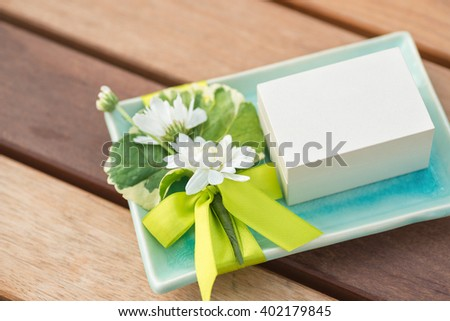 a small white box on decorated turquoise ceramic tray with white flowers and green ribbon - stock photo