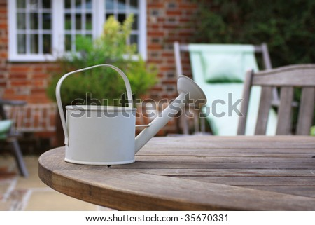 A small white/cream watering can set atop a wooden patio table in front of a stone faced country cottage in soft focus to the background. - stock photo