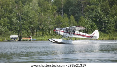 A small white floatplane lands on a Minnesota lake in summer - stock photo