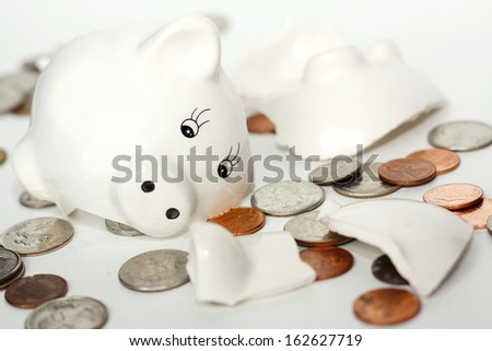 a small white piggy bank has just been broken into pieces and coin money is lying scattered around it, isolated on a white background - stock photo