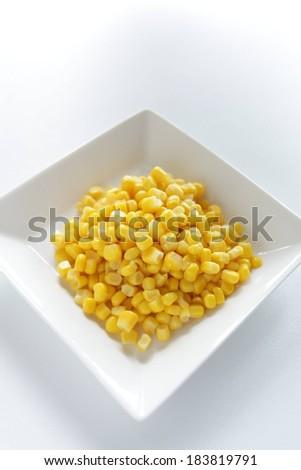 A small white square dish of corn kernels. - stock photo