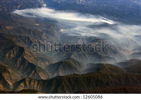 A small wild fire in the San Bernardino mountains fills the valleys of neighboring peaks with low lying smoke on October 21, 2007. - stock photo