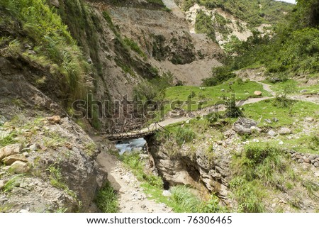 A small wooden bridge crossing a rocky canyon, on the Salkantay Trail. Near Mollepata, Peru. - stock photo