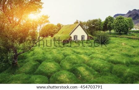 A small wooden church and cemetery Hofskirkja Hof, Skaftafell Iceland. Scenic sunset through tree crowns. - stock photo