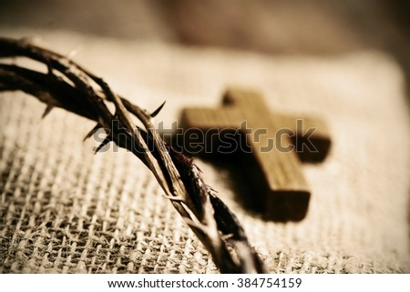 a small wooden cross and a depiction of the crown of thorns of Jesus Christ on a burlap fabric background - stock photo