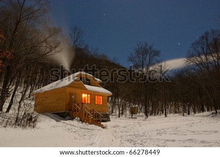 a small wooden house in a snowy forest - stock photo