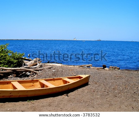 A small wooden rowboat sits on the shore of Lake Erie - stock photo