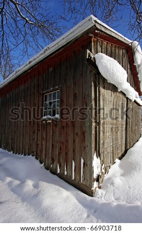 a small wooden shed on sunny winter day - stock photo