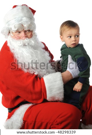 A small, worried boy looking over his shoulder as Santa holds him on his lap.  Isolated on white. - stock photo
