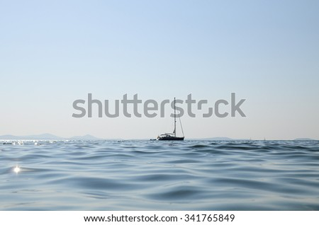 A small yatch in the middle of the sea in a clear sky day - stock photo