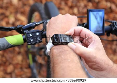 A Smart-watch and a E-Mountain-bike - stock photo