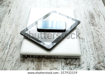A smartphone, a tablet computer and a laptop computer on a wooden desktop.