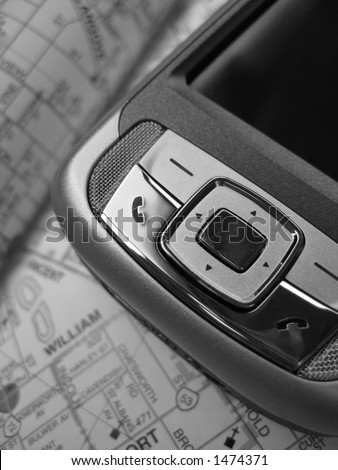 A Smartphone PDA with GPS capability. The background is a street map. This is a black and white image. - stock photo