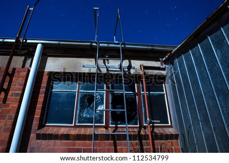 A smashed window at an old abandoned factory at night. Long exposure lit by moon light. - stock photo