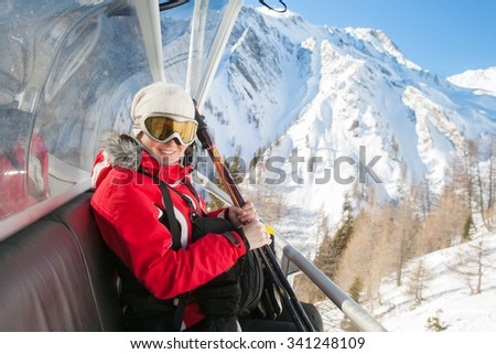 A smile woman is sitting on chairlift in mountain resorts. - stock photo