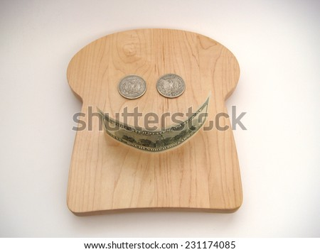 A Smiley Face Formed With Two Silver US Morgan Dollars For The Eyes And A United States Hundred Dollar Note For The Mouth Resting On A Bread Shaped Cutting Board Over White With Slight Vignetting. - stock photo