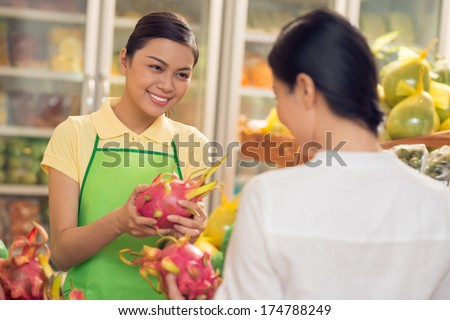 A smiley saleswoman giving a ripe pitaya fruit to the customer in the supermarket  - stock photo