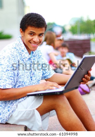 A smiling african american man on his laptop - stock photo