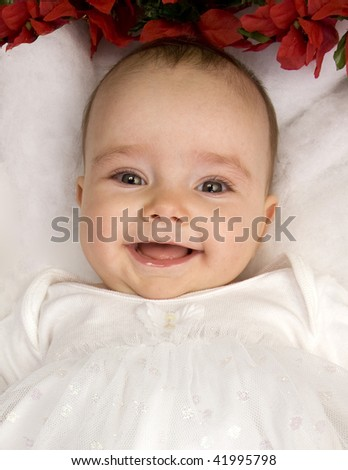 A Smiling Angelic Infant Girl Dressed In White Surrounded By Christmas Flowers - stock photo