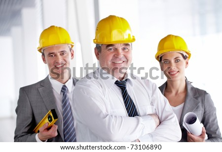 A smiling architect in helmet against his two colleagues - stock photo