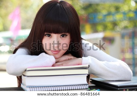 A smiling Asian student is studying. - stock photo