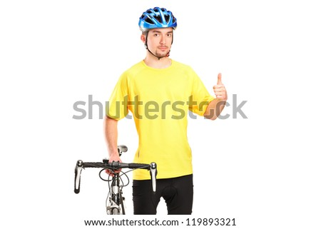 A smiling bicyclist posing next to a bicycle and giving thumb up isolated on white background