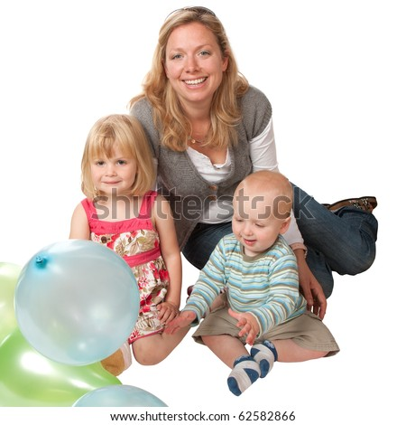 A smiling blond woman with a 4 year old girl and 1 year old boy.  The little boy is playing with some balloons. (The children are brother and sister, the adult is not their mother)