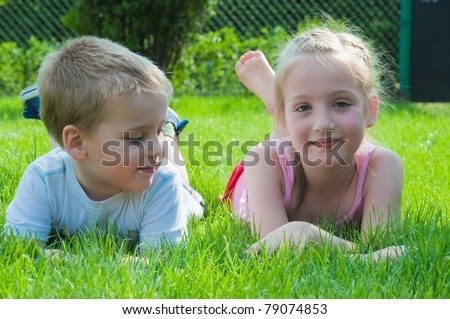 a smiling boy and a little girl are lying on the grass in the park