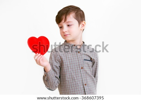 A smiling boy in a plaid shirt with a red heart in his hands.