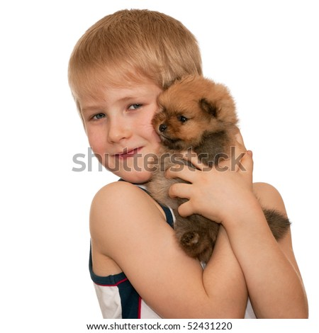 A smiling boy is holding a little puppy; isolated on the white background