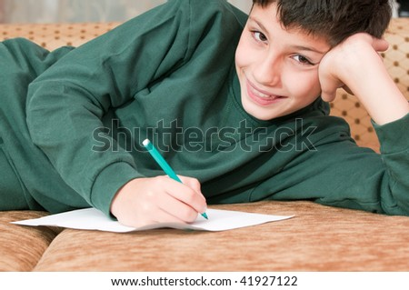 A smiling boy is writing a letter
