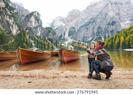 A smiling brunette mother kneels next to her daughter, pointing up. In the background, wooden boats float on the water, autumn colours, the Dolomite mountains, and forest. - stock photo