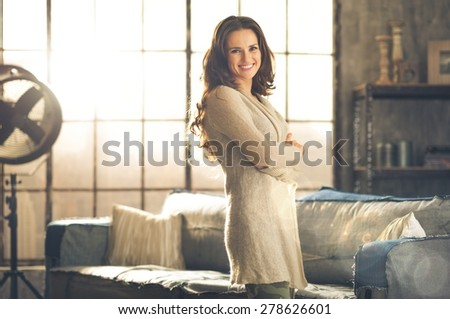 A smiling brunette woman in comfortable clothing is standing in a loft living room, arms crossed. Urban chic loft decoration details. - stock photo