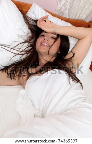 A smiling brunette woman relaxing in bedroom - stock photo