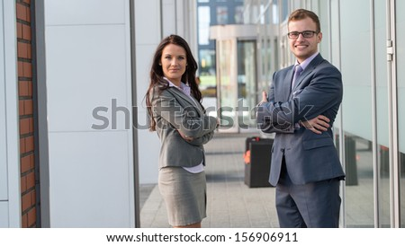 A smiling business man and woman are posing.