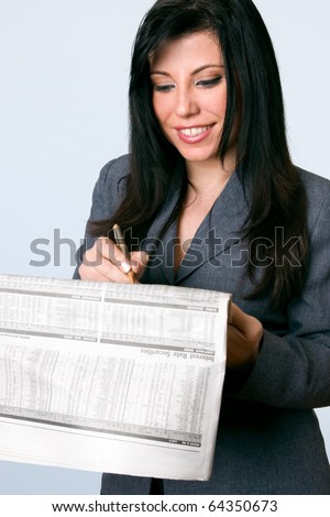 A smiling business woman checking the finance, bonds, shares, securities,  pages of a national newspaper.  Company data has been blurred for privacy - stock photo