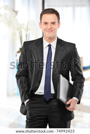 A smiling businessman holding a laptop and posing in his office - stock photo