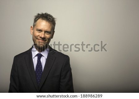a smiling, businessman looks happily into the camera - stock photo