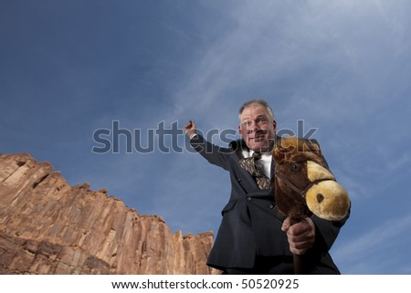 A smiling businessman rides a stick horse with one arm pointing to the sky in a desert landscape. Horizontal shot. - stock photo