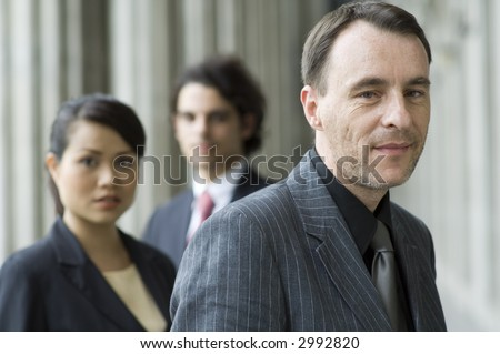 A smiling businessman standing in front of two colleagues (shallow depth of field used)