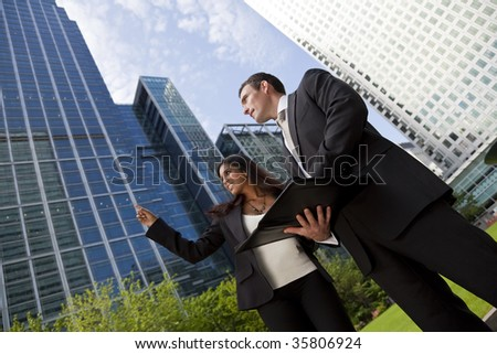A smiling businesswoman and her male colleague taking part in a happy business meeting outside in a modern city environment