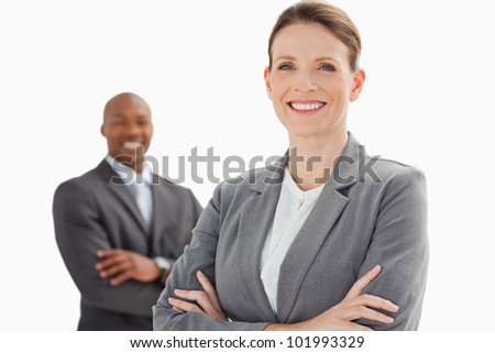 A smiling businesswoman and man with their arms crossed - stock photo