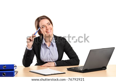 A smiling businesswoman in thought posing in her office - stock photo