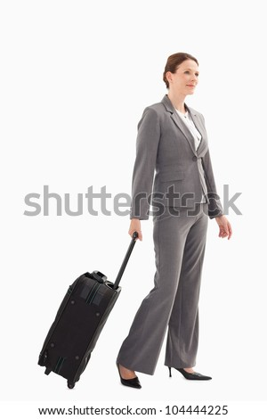 A smiling businesswoman with a suitcase is walking