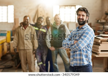 A smiling carpenter with his staff in the background - stock photo