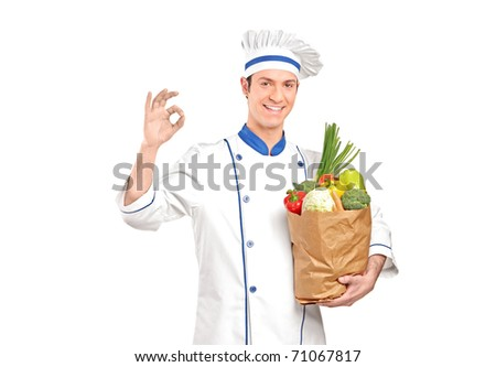 A smiling chef gesturing delicious hand sign and holding a grocery bag full with vegetables isolated on white background - stock photo