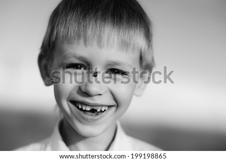 A smiling child without teeth with a ladybird on his cheek close up,  black-and-white photo - stock photo
