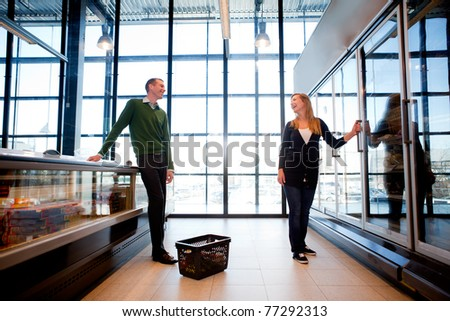 A smiling couple flirting in the supermarket - stock photo