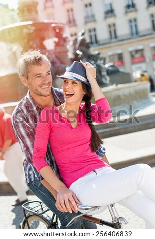 A smiling couple is riding a retro bike in the city center. The grey hair man is riding the bike while the woman is sitting on the handlebar. She is wearing a pink top and a blue hat. - stock photo